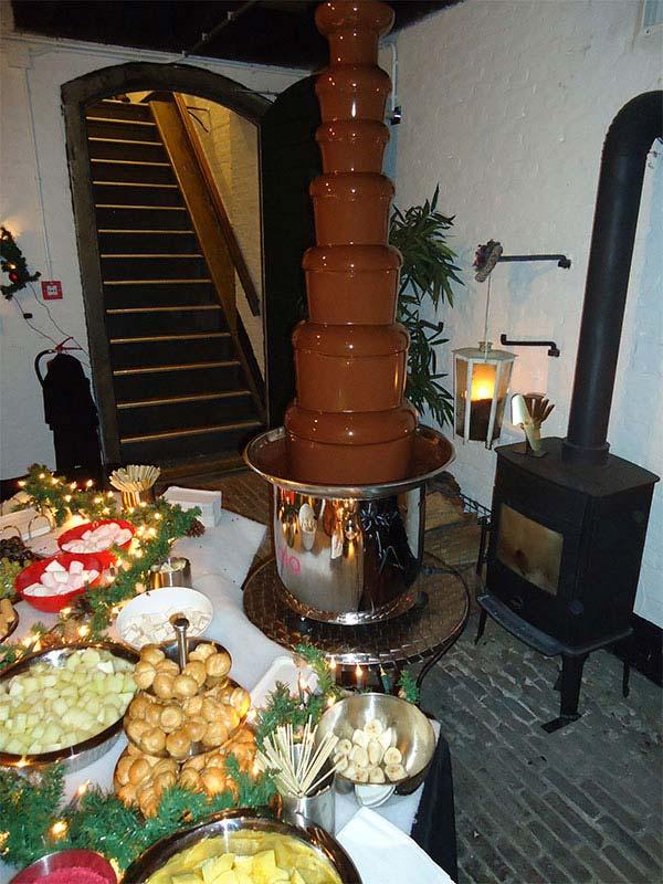 Een gezellig idee om tijdens de kerstborrel met familie, vrienden en collega's een aardbei of soesje in de chocoladefontein te dompelen.